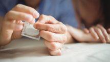 Mão de homem abrindo uma embalagem de preservativo masculino.
