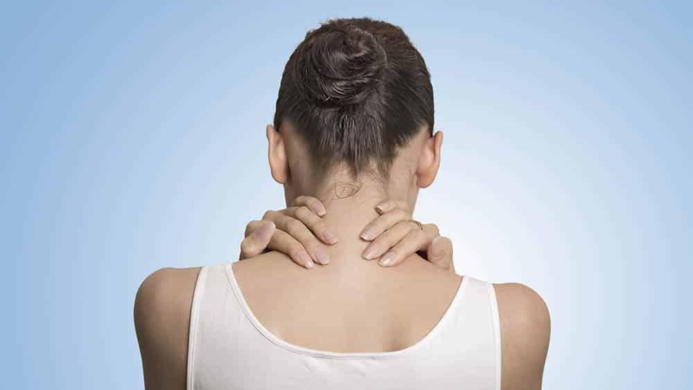 Mulher de costas massageando a nuca aliviando a dor.