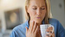 Mulher segurando uma xícara e, com a outra mão, segurando a garganta demonstrando dor.