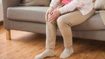 Mulher mais velha sentada segurando um dos joelhos sugerindo dor no local, comum durante crises de gota.