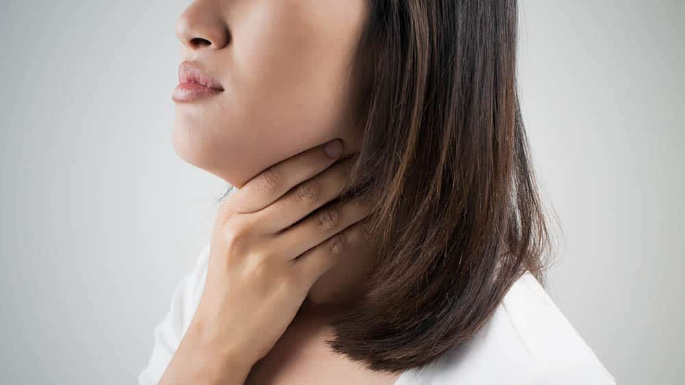 Mulher com a mão na própria garganta indicando dor, principal sintoma da amidalite.