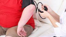 Médica medindo a pressão de uma pessoa obesa.