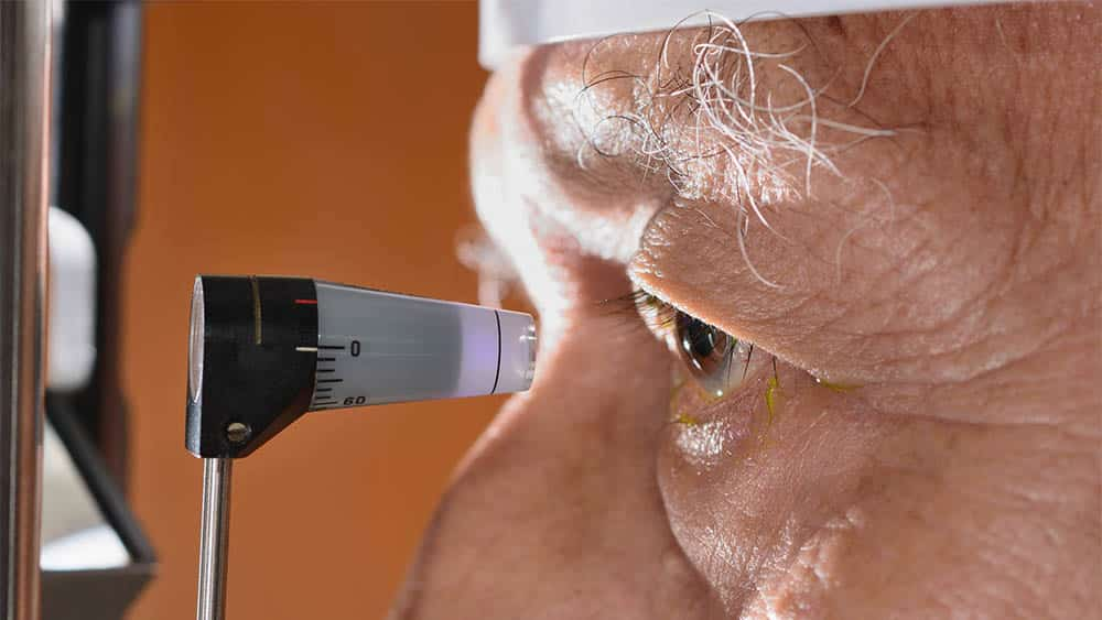 Close em olho de homem de perfil fazendo exame de pressão intraocular.