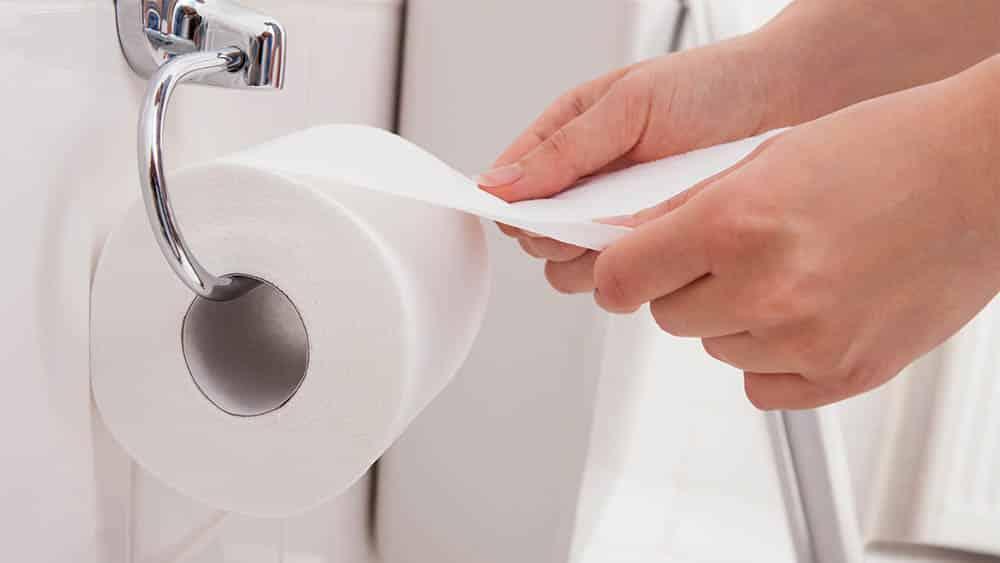 Close nas mãos de uma mulher desenrolando papel higiênico em um banheiro.