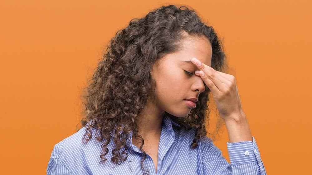 Mulher pressionando com a mão a região entre os olhos, local típico de dor em caso de sinusite.