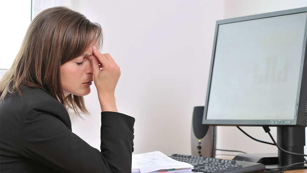 Mulher em frente ao computador pressionando a região entre os olhos, indicando vertigem ou tontura.