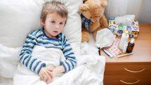 Criança doente em repouso na cama com medicamentos no criado-mudo ao lado.