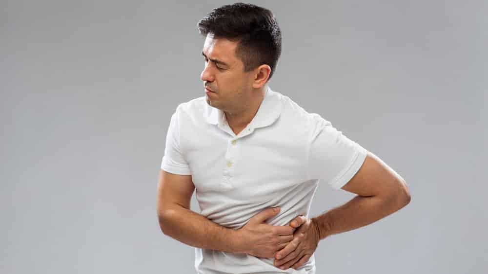 Homem em fundo cinza pressionando a lateral do abdômen com as duas mãos e expressando dor.
