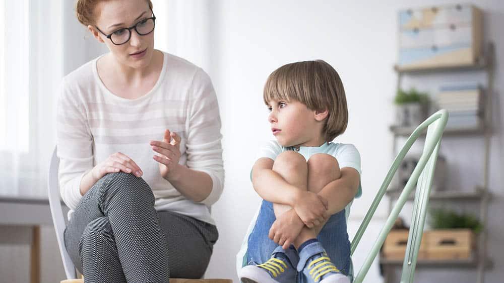 Terapeuta falando com menino enquanto ele não faz contato visual. veja as causas do autismo