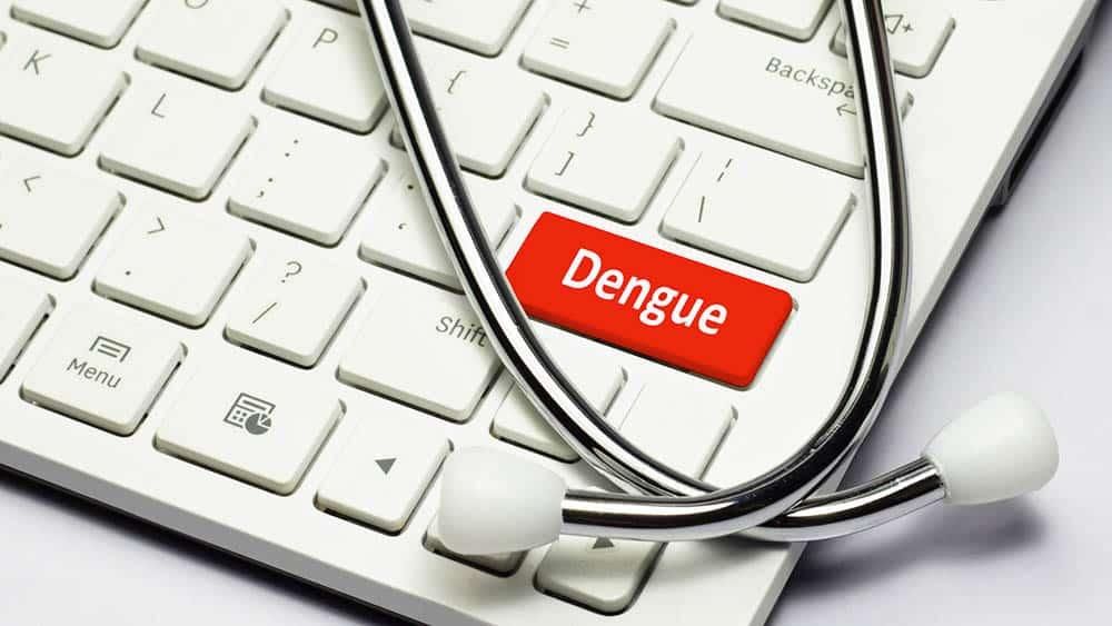 Estetoscópio sobre teclado com uma tecla vermelha escrito dengue.