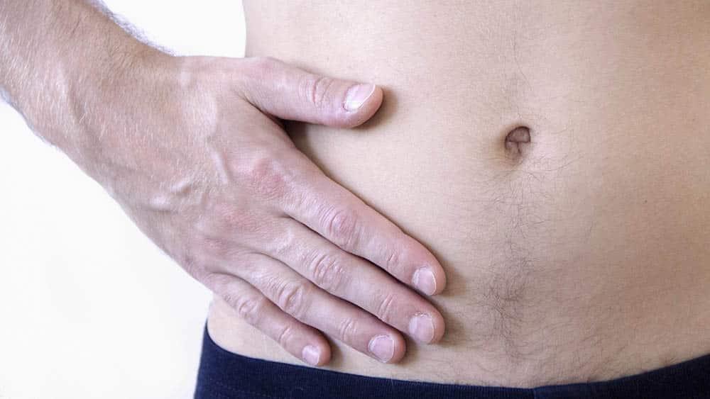 Close em abdômen de homem com mão sobre a região inferior direita, do apêndice.