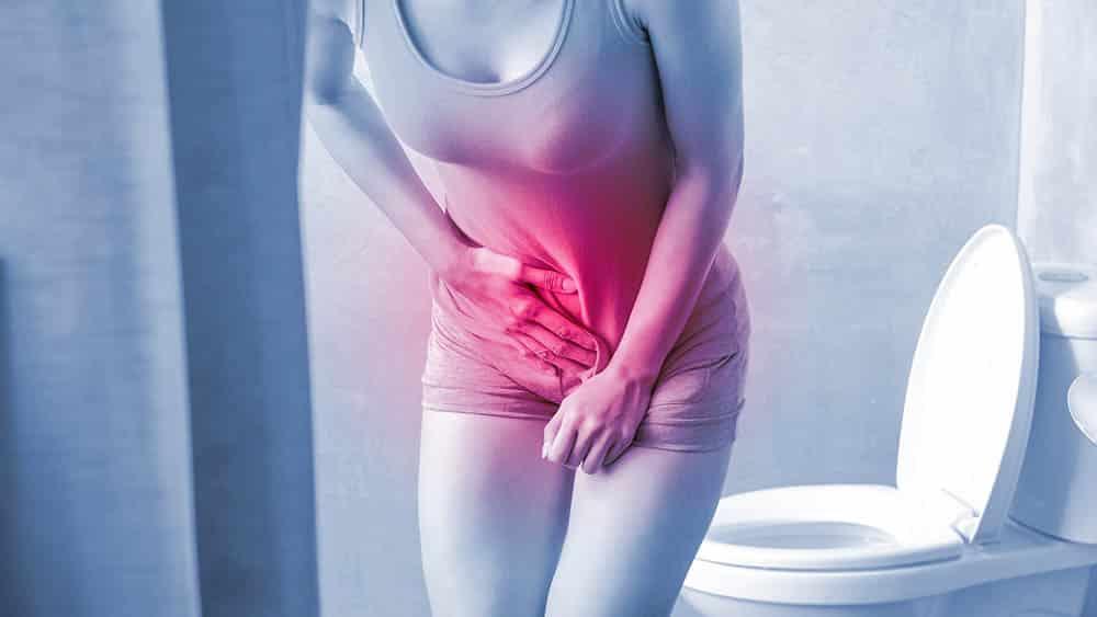 Mulher em um banheiro com a mão na região da bexiga indicando vontade de urinar.