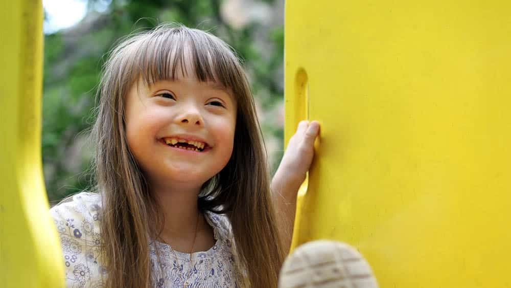 Menina com síndrome de Down brincando em playground.