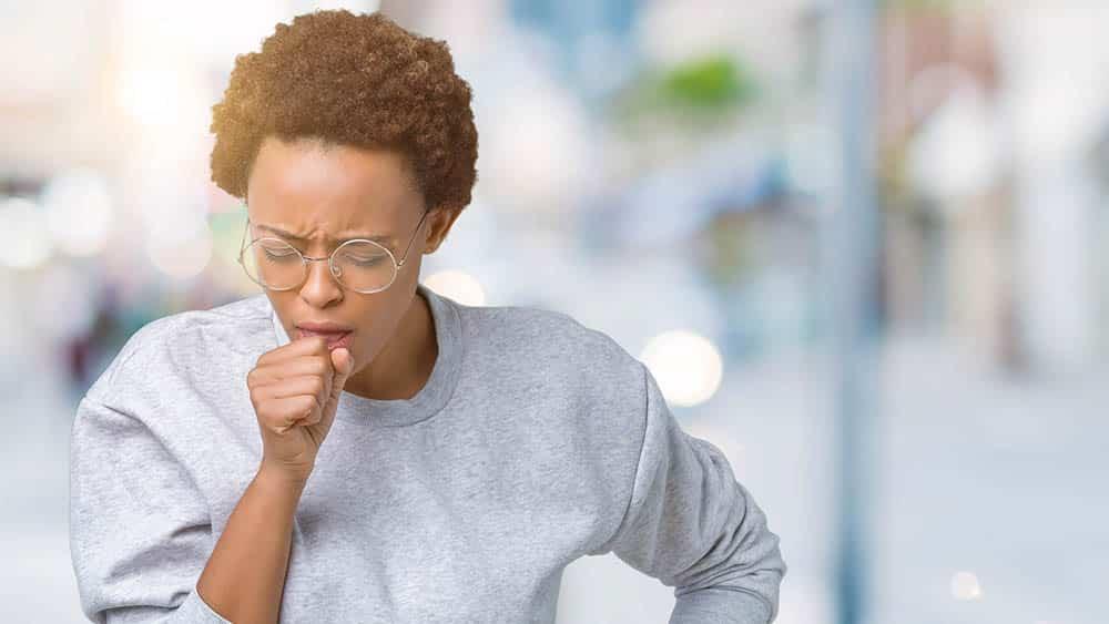 Mulher tossindo na rua.