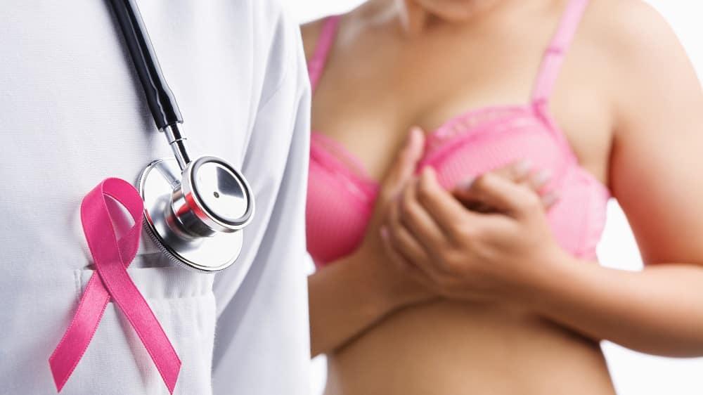 Médico com o laço rosa que representa a luta contra o câncer de mama, enquanto mulher toca o próprio seio