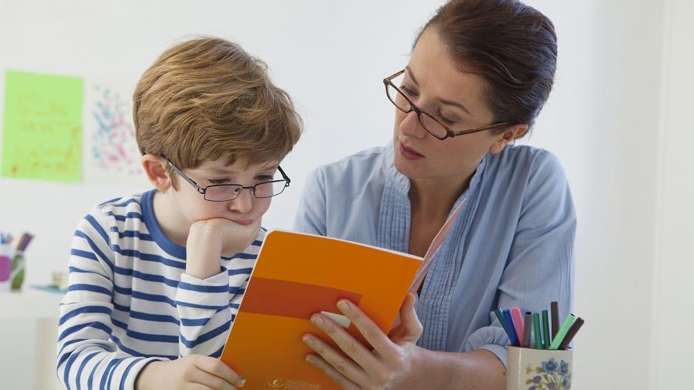 Criança com dislexia sendo ajudada pela mãe