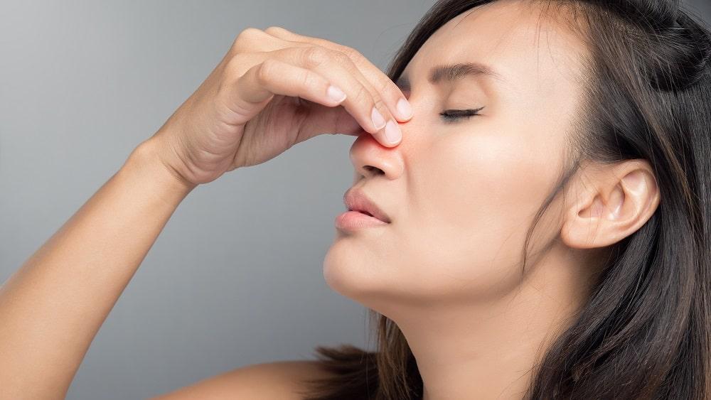 Mulher com congestão, um dos sintomas nasais crônicos
