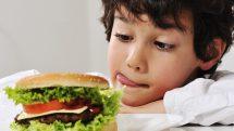 Menino olhando hambúrguer.