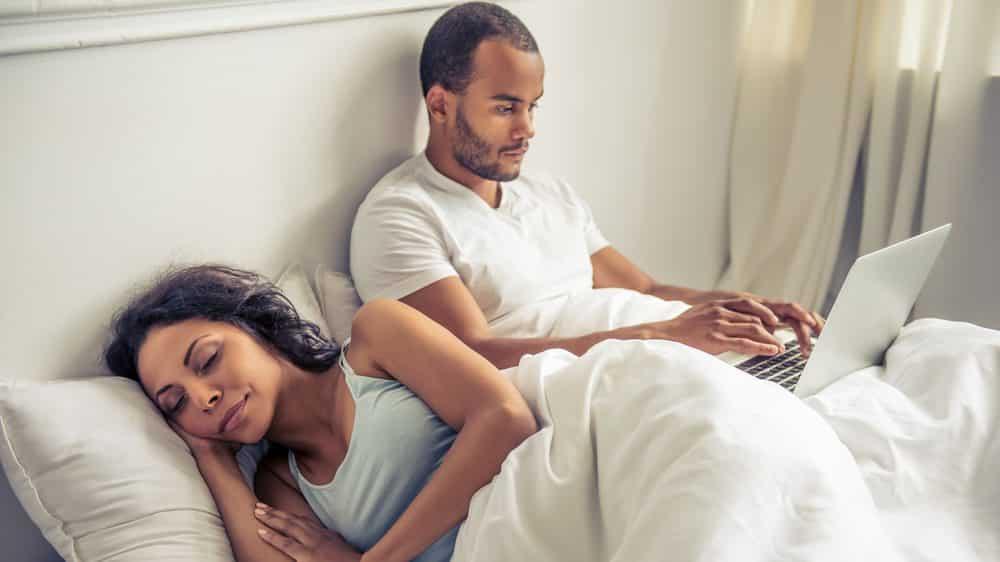 mulher dorme na cama ao lado de homem que usa computador e tem relógio biológico diferente