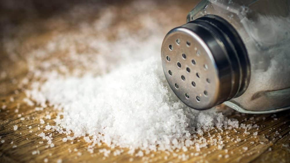 saleiro com monte de sal ao lado. quantidade de sal na dieta deve ser moderada