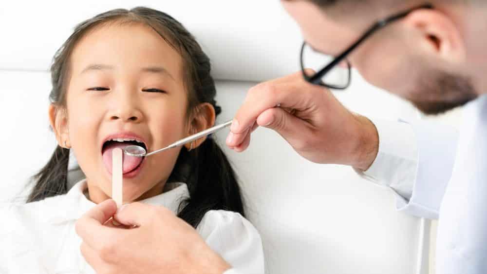 dentista examina boca de menina. Micróbios da boca causam vários problemas bucais