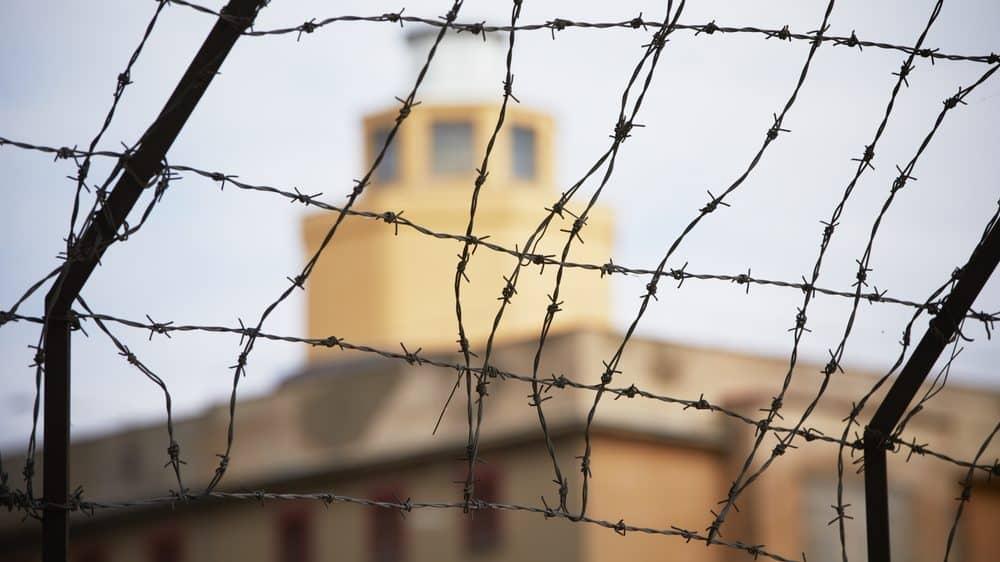 torre de penitenciária cercada por arame farpado. veja as raízes sociais da violência