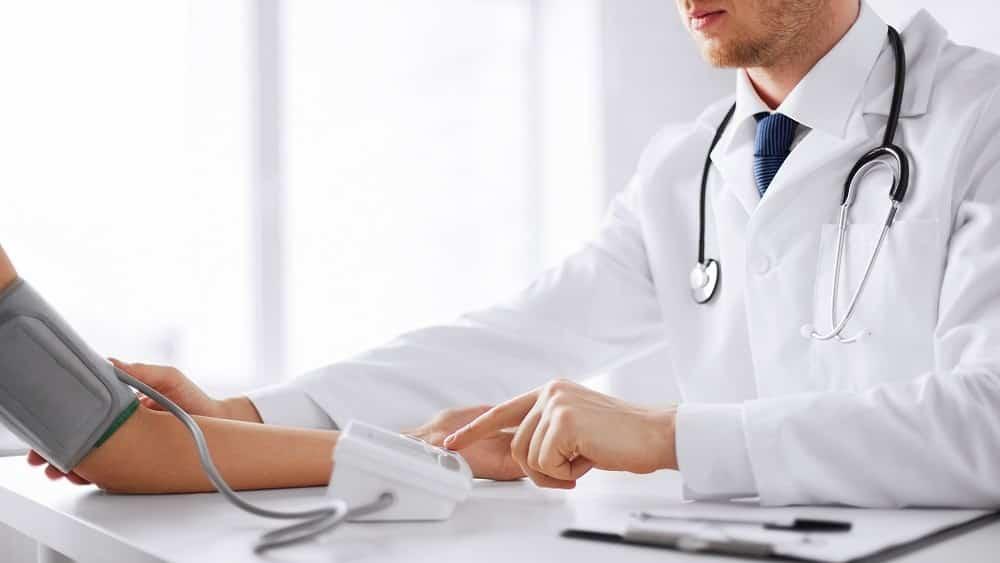Médico medindo a pressão arterial de paciente.