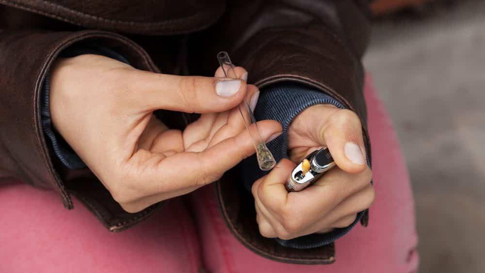 jovem fuma maconha em cachimbo de vidro. droga pode gerar prazer compulsivo