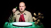 homem com cara de fome diante de prato vazio