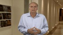 Drauzio Varella de mãos cruzadas em um corredor falando sobre tumores