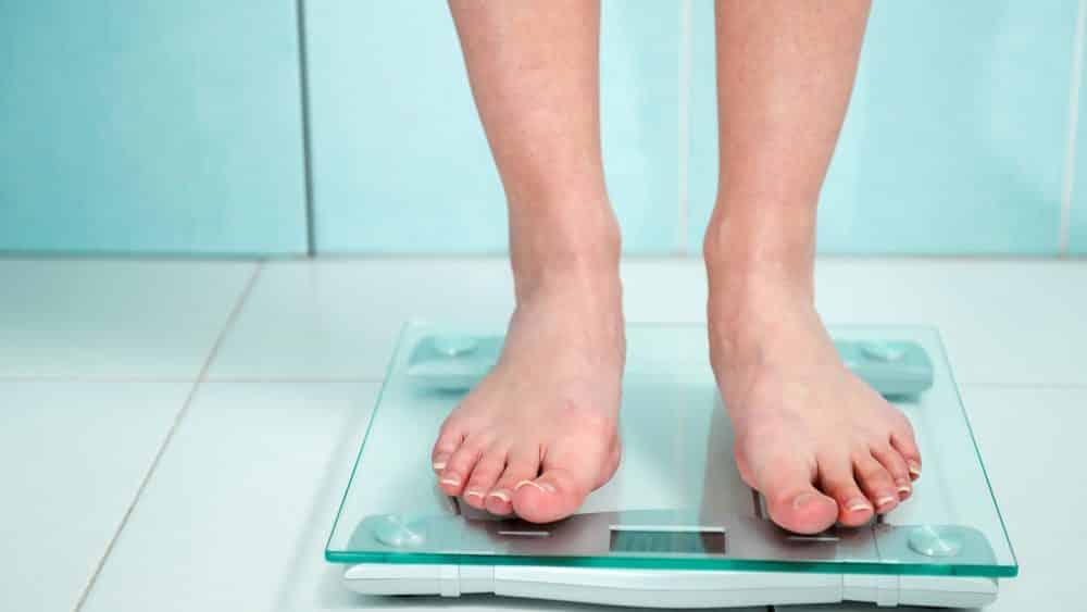 close de pés de mulher se pesando na balança