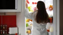 mulher abrindo a geladeira à noite à noite