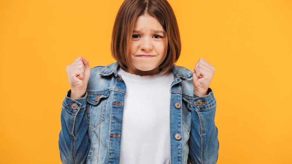 menina com rosto franzido e punho cerrado, nervosa. Síndrome de Tourette causa tiques incontroláveis