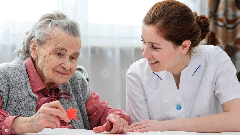 idosa com demência avançada monta quebra-cabeça com enfermeira