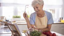 mulher idosa cozinha olhando livro de receita. dieta e envelhecimento estão relacionados.