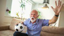 homem idoso torcendo no sofá de casa, enquanto segura bola de futebol