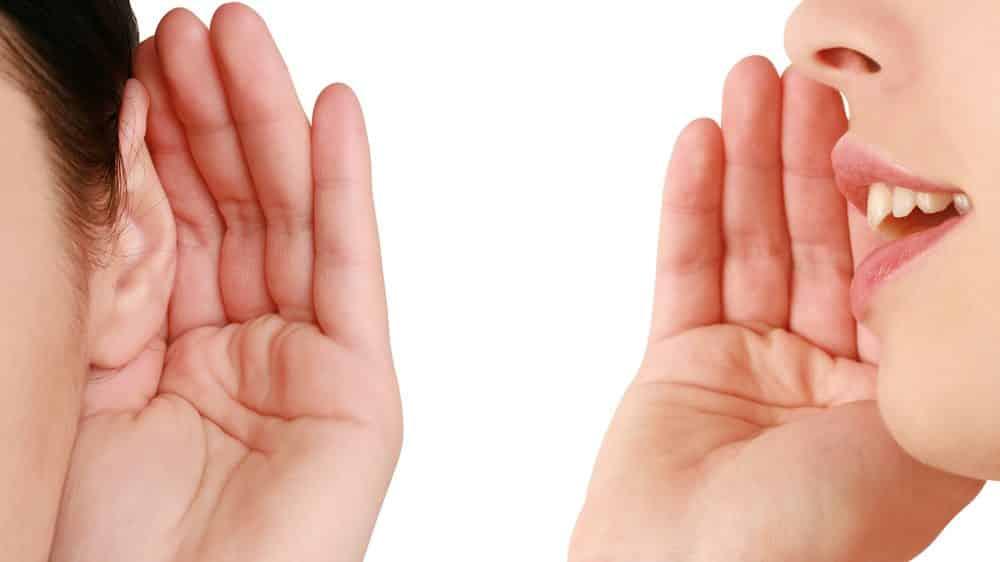 mulher fala, com mão na boca, e outra escuta, com mão na orelha. Origem da linguagem é tema de debate