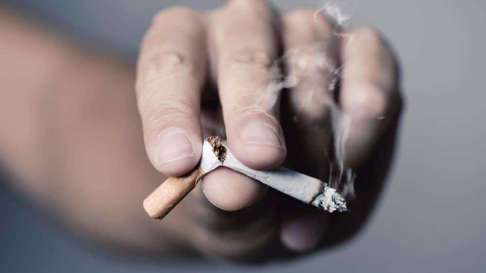 close de mão de fumante quebrando cigarro, como um viciado arrependido