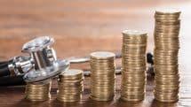 estetoscópio ao lado de moedas empilhadas. Evolução do tratamento contra o câncer encareceu a medicina