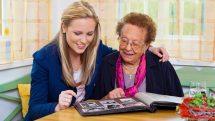 idosa olha álbum de fotos acompanha de mulher jovem. Alzheimer atinge mais mulheres
