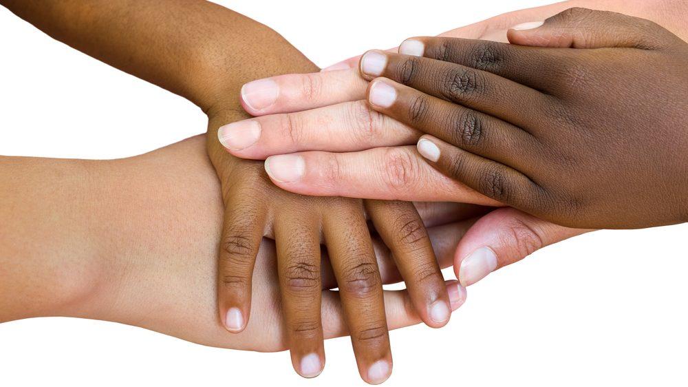 close de mãos de crianças de raça diferente juntas.