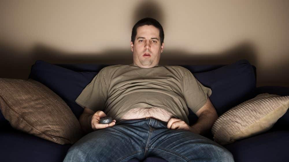 homem sedentário e com sobrepeso sentado no sofá, assistindo à TV