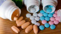 close em frascos abertos, com comprimidos de vitaminas coloridos caídos sobre uma mesa