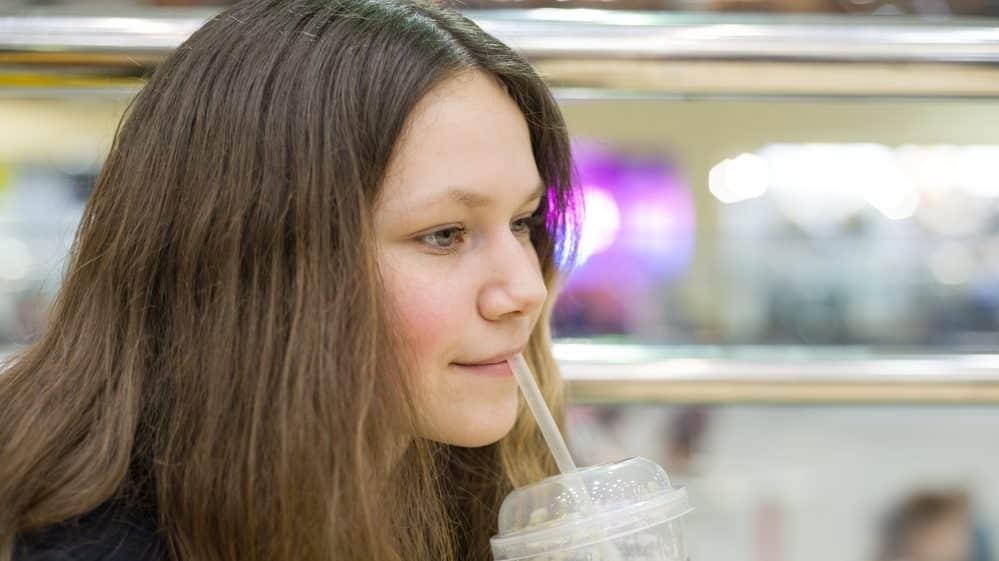 menina jovem toma suco. obesidade na adolescência traz riscos na vida adulta