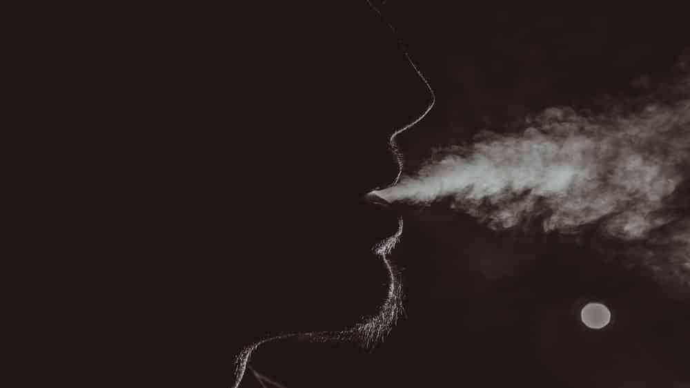 jovem de perfil sopra fumaça. oxi e crack são drogas fumadas