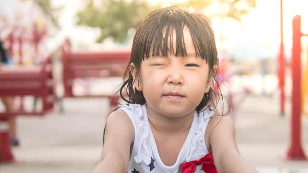 Menina asiática em parquinho com um olho fechado, indicando um tique.