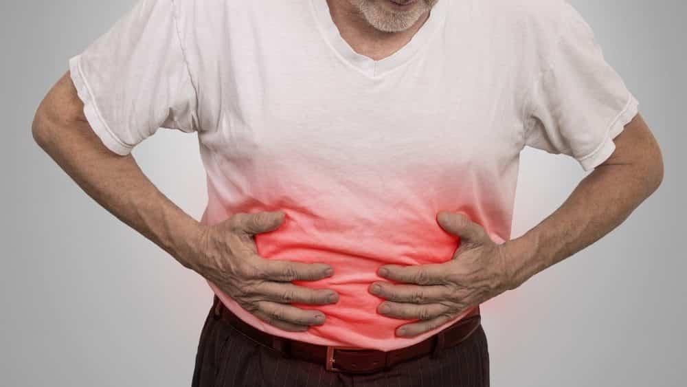 Homem com mãos no abdômen em sinal de dor, um dos sintomas da doença de Crohn.