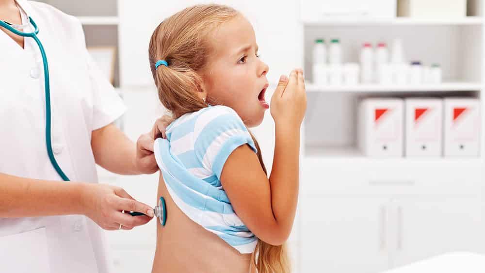 Menina tossindo enquanto médica está com estetoscópio nas suas costas.