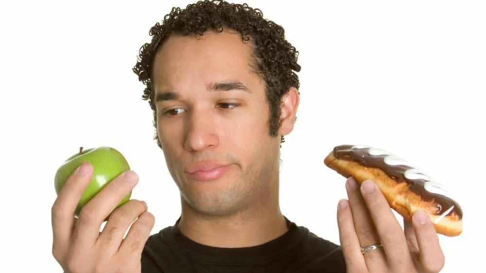 rapaz segura maçã em uma mão e bomba de chocolate em outra. há relação entre obesidade e dieta