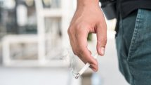 mão de homem segurando cigarro aceso
